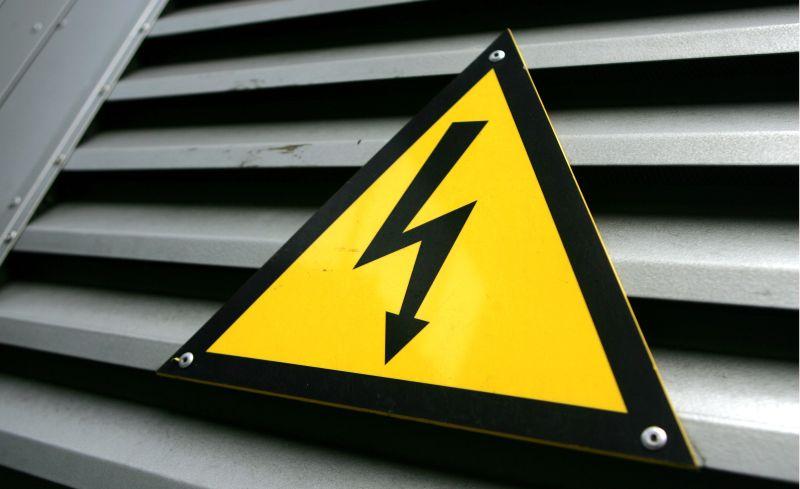 """Emaljēta brīdinājuma zīme """"Uzmanību! Elektrība"""" par augsto spriegumu pie transformatora apakšstacijas durvīm."""
