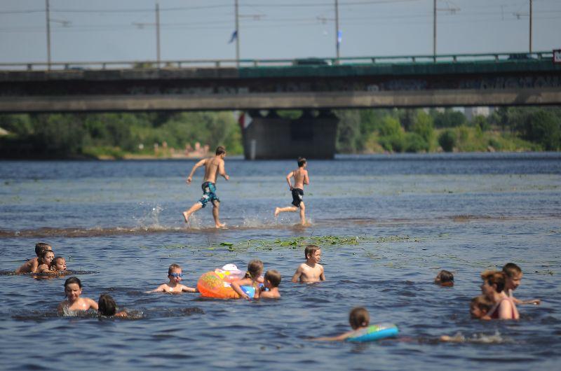 Cilvēki peldas peldvietā Lucavsalā.