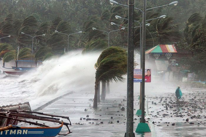 A resident (R) walks past high waves pounding the sea wall amidst strong winds as Typhoon Haiyan hit the city of Legaspi, Albay province, south of Manila on November 8, 2013.  One of the most intense typhoons on record whipped the Philippines on November 8, killing three people and terrifying millions as monster winds tore roofs off buildings and giant waves washed away flimsy homes.AFP PHOTO/CHARISM SAYAT