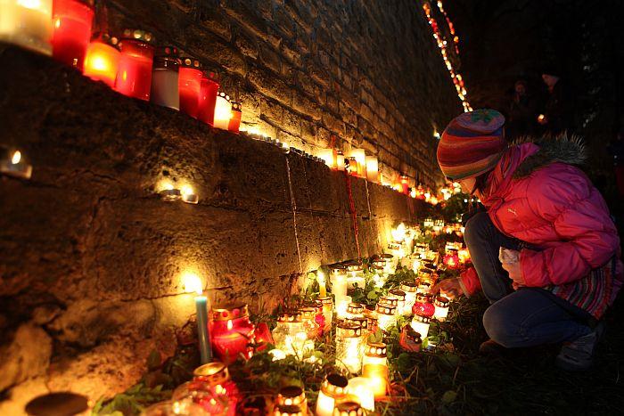 Cilvēki noliek sveces 11.novembra krastmalā par godu Lāčplēša dienai.
