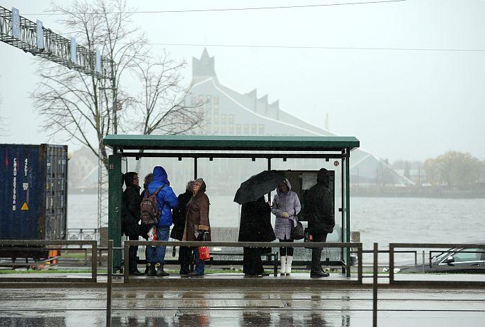 Cilvēki sabiedriskā transporta pieturvietā lietus un krusas laikā pilsētā.