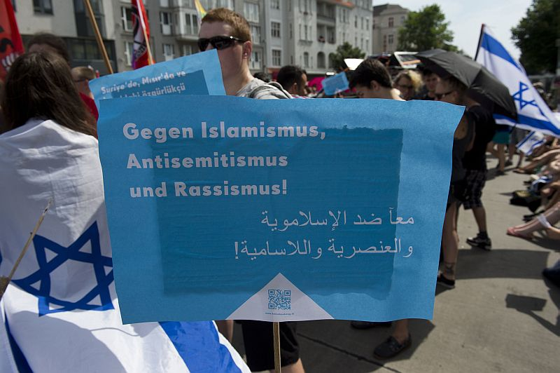 "Demonstrators protesting against the Quds Day rally display a placard reading ""Against Islamism, Antisemitism and Racism"" in Berlin, Germany on August 3, 2013. Quds Day, initiated by the Iranian government in 1979, takes place every year on the last friday of Ramadan, to express solidarity with the Palestinian people and to oppose Israel's control of Jerusalem. AFP PHOTO / JOHN MACDOUGALL"
