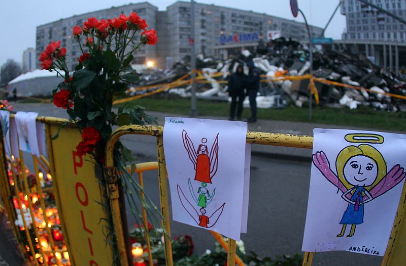 Paintings and flowers are fixed on a fence near the accident site of a collapsed Maxima supermarket in Riga on November 23, 2013, where the roof of the building caved in on shoppers on November 21. Latvia mourned its dead after the supermarket roof collapse left at least 53 dead in Riga and investigators launched a criminal probe into one of Europe's most deadly building disasters. The small Baltic state of two million began three days of grieving over the Thursday tragedy, Europe's third worst roof disaster in 30 years.    AFP PHOTO / PETRAS MALUKAS