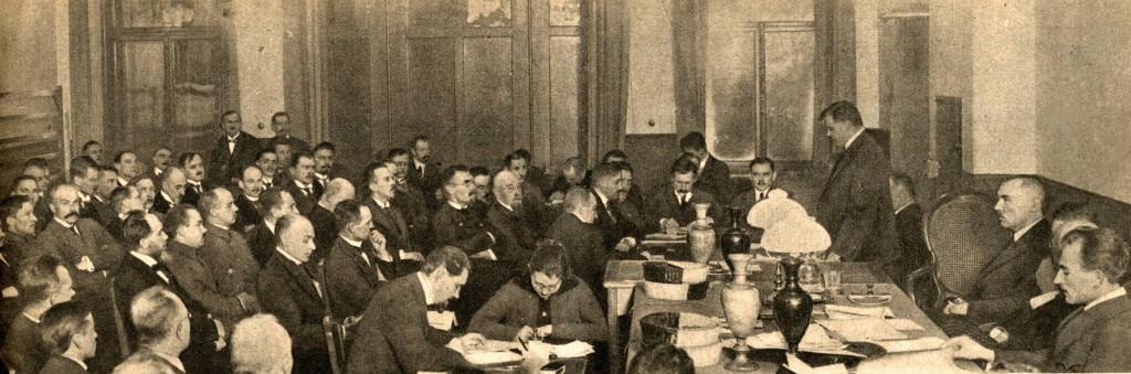 Pirmā Tautas padomes plenārsēde 1918. gada novembrī. No labās: stāv Ministru prezidents Kārlis Ulmanis, sēž Alberts Kviesis.