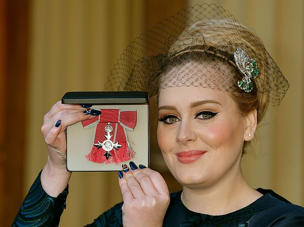 British singer-songwriter Adele Adkins holds her medal after being appointed a Member of the Order of the British Empire (MBE) for services to music presented to her by the Prince Charles, Prince of Wales during an investiture ceremony at Buckingham Palace in London on December 19, 2013.  AFP PHOTO / POOL / JOHN STILLWELL