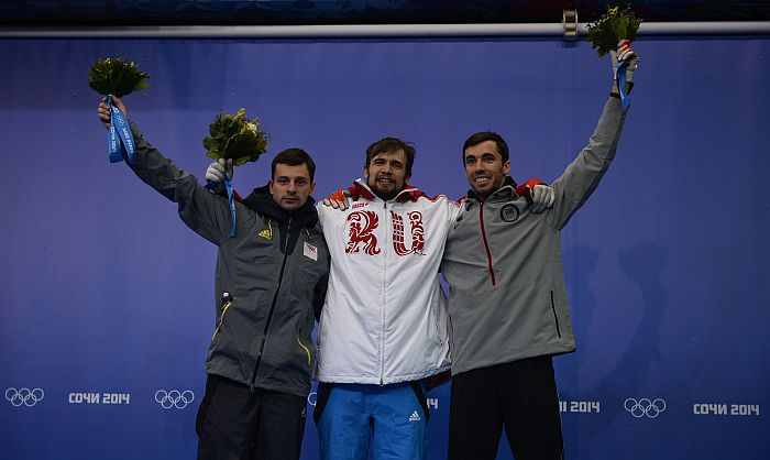 (From L) Latvia's silver medalist Martins Dukurs, Russia's gold medalist Alexander Tretiakov, and US bronze medalist Matthew Antoine stand on the podium of the Men's Skeleton Flower Ceremony at the Sanki Sliding Center in Rosa Khutor during the Sochi Winter Olympics on February 15, 2014. AFP PHOTO / LIONEL BONAVENTURE