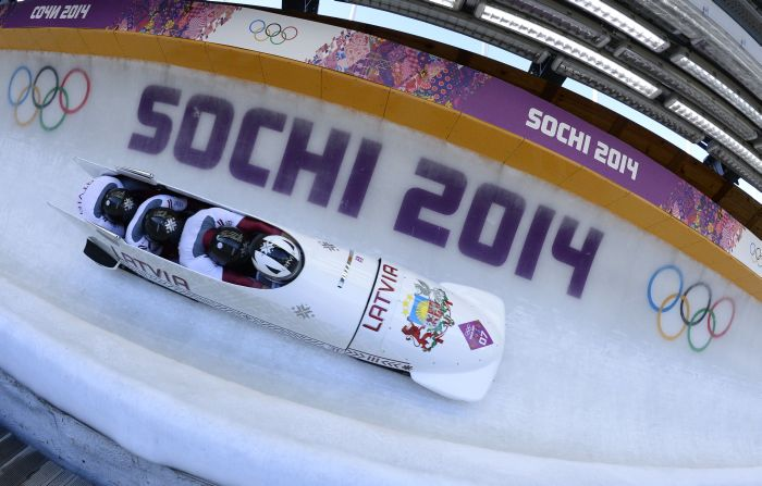 Silver Medallist, Latvia-1 four-man bobsleigh, pilot Oskars Melbardis, pushman Daumants Dreiskens, pushman Arvis Vilkaste and brakeman Janis Strenga compete in the Bobsleigh Four-man Heat 4 and final run at the Sanki Sliding Center during the Sochi Winter Olympics on February 23, 2014.    AFP PHOTO / LIONEL BONAVENTURE
