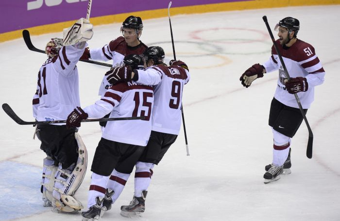 Latvian players celebrate a 3-1 victory during the Men's Ice Hockey Play-offs Switzerland vs Latvia at the Bolshoy Ice Dome during the Sochi Winter Olympics on February 18, 2014.  AFP PHOTO / ALEXANDER NEMENOV
