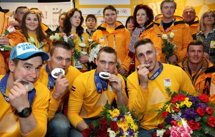 """Soču olimpisko spēļu sudraba medaļas ieguvēji bobslejisti Arvis Vilkaste (no kreisās), Daumants Dreiškens, Jānis Strenga un Oskars Melbārdis lidostā """"Rīga""""."""
