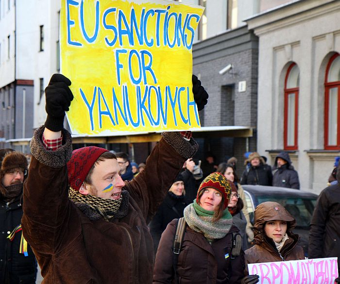 """A protestor holds a sign reading """" EU sanctions for Yanukovich"""" during the """"Stretch out your hand to Ukraine"""" demonstration against the escalation of anti-government protests in Ukraine on January 25, 2014 in Vilnius. The protestors built a human chain between the European Commission Representation office in  and the Ukraine Embassy in Lithuania.  AFP PHOTO / PETRAS MALUKAS"""