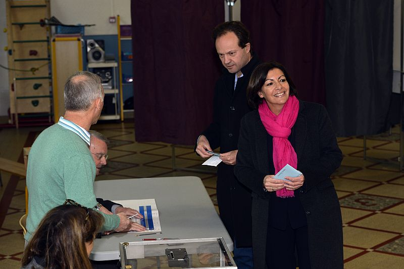 Paris Deputy Mayor and French Socialist party (PS) candidate for the Paris municipal elections, Anne Hidalgo,smiles before casting her ballot in the first round of the French municipal elections on March 23, 2014 at a polling station in Paris, next to her husband Jean-Marc Germain. Sunday's contest is the first nationwide vote since Socialist leader Francois Hollande was elected as president two years ago. AFP PHOTO / MIGUEL MEDINA