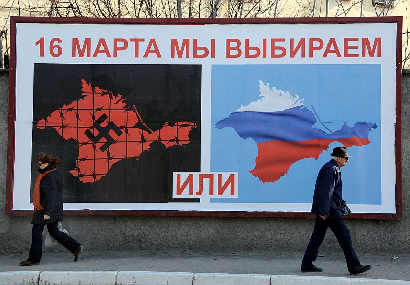 "People walk past a poster in Sevastopol on March 11, 2014 reading ""On March 16 we will choose either… or…"", depicting Crimea in red with a swastika and covered in barbed wire (L) and Crimea with the colors of the Russian flag. Pro-Moscow lawmakers in Crimea voted for independence from Ukraine on March 11 in a precursor to a referendum this weekend for the region to become part of Russia. AFP PHOTO/ VIKTOR DRACHEV"