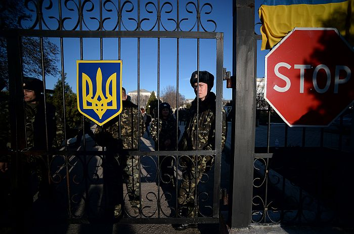 """Ukrainian soldiers look out through a gate near a """"stop"""" sign as they wait inside the Sevastopol tactical military brigade base near Belbek in Sevastopol on March 3, 2014. Russian forces have given Ukrainian soldiers an ultimatum to surrender their positions in Crimea or face an assault, a Ukrainian defence ministry spokesman said. """"The ultimatum is to recognise the new Crimean authorities, lay down our weapons and leave, or be ready for an assault,"""" said Vladyslav Seleznyov, the regional ministry spokesman for the Crimea. AFP PHOTO / FILIPPO MONTEFORTE"""