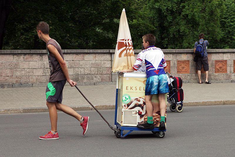 Zēni ar saldējuma tirgošanas kasti.