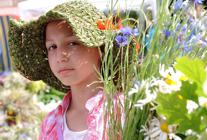 Meitene ar jāņuzālēm Zāļu tirgū Doma laukumā.