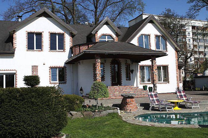 Māja no ārpuses ir sniegbalta, stūrīši apdarināti ar zāģētiem sarkanajiem ķieģeļiem, pagalmā – baseins, kur karstās vasaras dienās veldzēties
