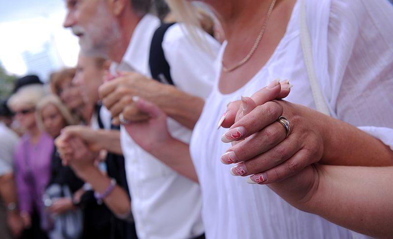 """Cilvēki sadevušies rokās Baltijas ceļam veltītās piemiņas plāksnes """"Pēdas"""" atklāšanas pasākuma laikā Kaļķu un Vaļņu ielas krustojumā."""