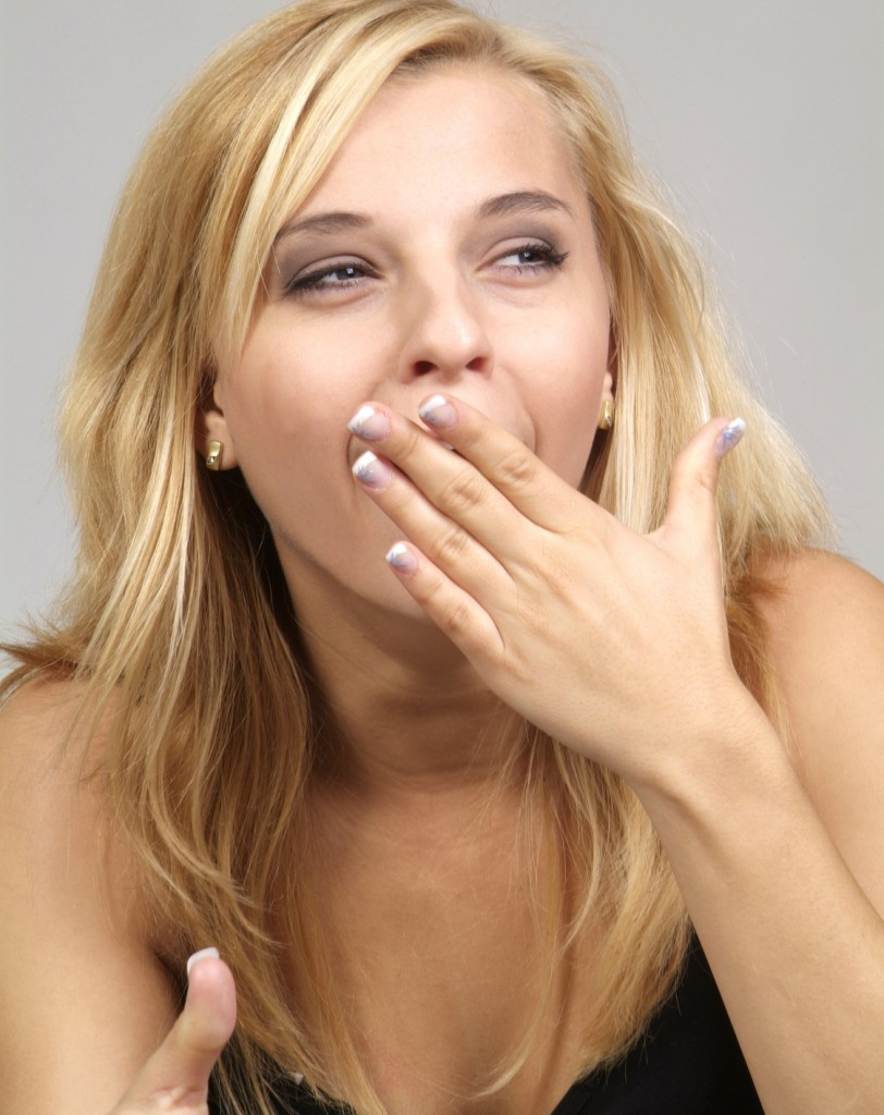 a pretty blond woman with hand and open mouth
