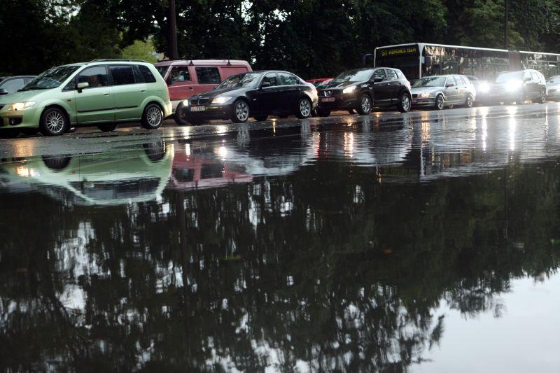 Mašīnas ūdens peļķēs pēc spēcīgā lietus.