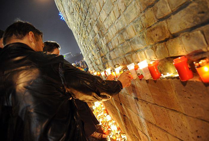 Cilvēki noliek svecītes Lāčplēša dienā pie Rīgas pils mūra 11.novembra krastmalā.