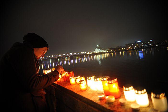 Cilvēki noliek svecītes Lāčplēša dienā pie Daugavas 11.novembra krastmalā.