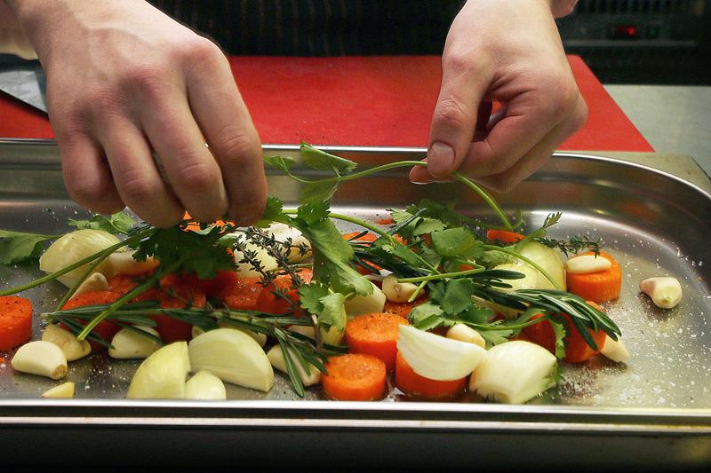 6. Sarullēto jēra cisku cep garšsakņu un dārzeņu gultā. Uz pannas uzlej nedaudz olīveļļas, lai sākumā gaļu nepierauj pie pannas (daudz ne, jo no gaļas tecēs tauki, kā arī sula no dārzeņiem). Tad kārto lielos gabalos sagrieztus burkānus, kartupeļus, selerijas sakni, sīpolus, kā arī ķiploku daiviņas, timiānu, rozmarīnu, smaržīgos piparus, lauru lapas un koriandru. Vēl var pievienot kāli, rutku, vienīgi nav ieteicams likt bietes, jo tās iekrāsos gaļu un pārējos dārzeņus. Dārzeņus griež lielos gabalos tādēļ, lai trīs stundās cepeškrāsnī tie nesaplok un neapdeg. Arī koriandra zaļās lapiņas var apdegt, tāpēc tās liek zem cepeša vai tuvāk sāniem. Kad cepetis nāk gatavs, ap to kārto mazus kartupelīšus, tie savilksies ar cepeša sulu un iegūs ideālu garšu. Savukārt zem cepeša noliktās saknes ieber katlā un sautē ar saldo krējumu. Sanāk tāds kārtīgs svētku ēdiens.