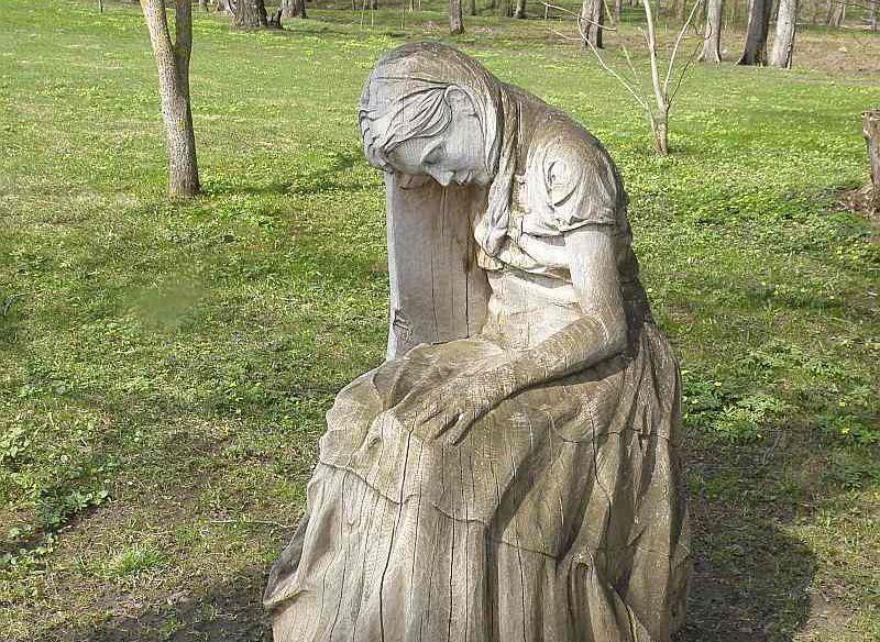 """""""Sērojošās Jadvigas"""" skulptūra, kas veidota no vētras nogāztā ozola Varakļānu muižas parkā."""