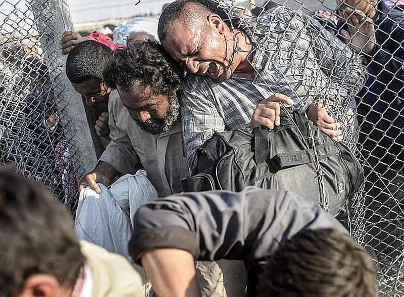 Sīriešu bēgļi izlaužas caur žogu Turcijas un Sīrijas pierobežā. Turcija pagājšnedēļ paziņojusi, ka ieviesīs pasākumus, lai ierobežotu bēgļu plūsmu.