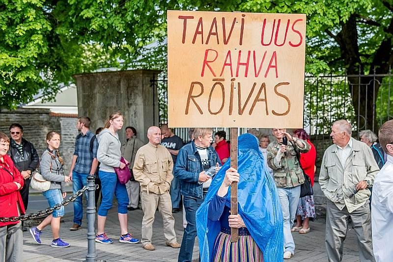 """Protestu pret valdības plāniem """"brīvprātīgi"""" uzņemt afrikāņu bēgļus pagājšnedēļ rīkoja Igaunijas Konservatīvā tautas partija. Uzraksts uz plakāta: """"Tāvi jaunais tautas tērps"""". (Izmantota vārdu spēle ar Igaunijas premjerministra Tāvi Reivasa uzvārdu, jo """"rõivas"""" igauņu valodā nozīmē """"apģērbs, kostīms"""".)"""