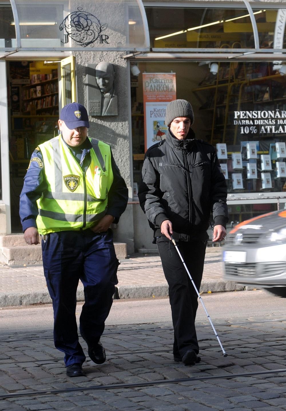 """Latvijas Neredzīgo biedrības neformālās jauniešu grupas """"Pozitīvs"""" dalībnieks Mārtiņš Vizulis sadarbībā ar Rīgas ceļu policiju organizētajā reidā Krišjāņa Barona ielā pārbauda, vai autovadītāji ir informēti par rīcību, ja neredzīgs cilvēks ar balto spieķi šķērso ielu."""