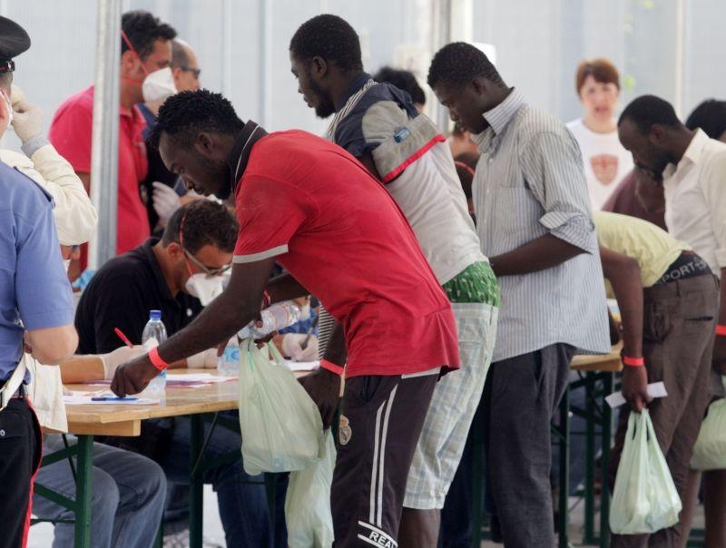 Migranti aizpilda identifikācijas dokumentus Palermo ostā Itālijā.