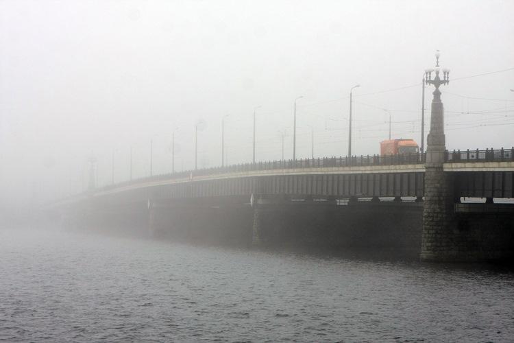 Akmens tilts miglā.