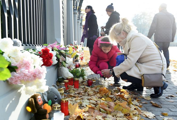 Cilvēki noliek ziedus pie Krievijas vēstniecības ēkas Rīgā traģiskajā aviokatastrofā Ēģiptē bojāgājušo piemiņai.