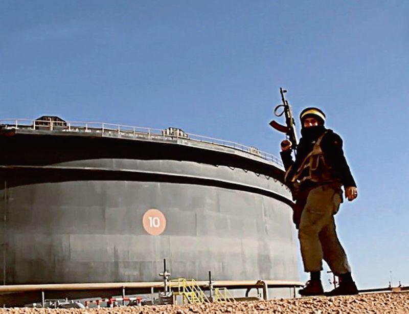 ISIS propagandas foto: lielākajā naftas glabātavā Lībijā maskējies ISIS kaujinieks ar AK-47 automātu pozē pie naftas uzglabāšanas tvertnes Sidrā.