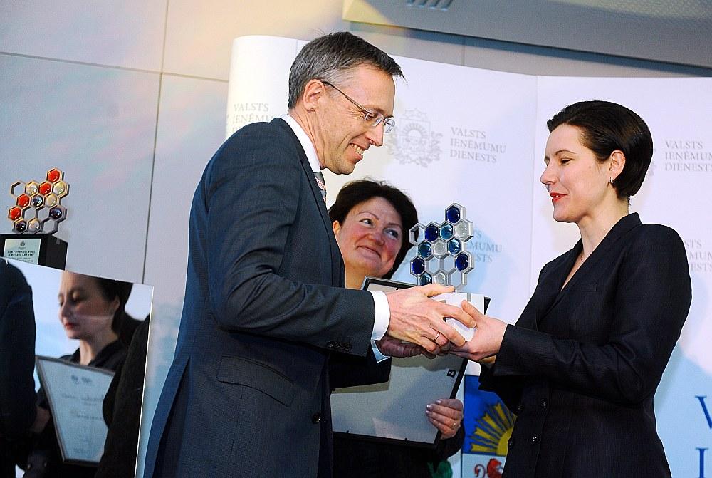 """Labākais pelnītājs – SIA """"Mikrotīkls"""". Finanšu ministre Dana Reizniece-Ozola pasniedz balvu 2015. gada lielākajam eksportētājam uz trešajām valstīm uzņēmuma līdzīpašniekam Arnim Riekstiņam VID Lielo nodokļu maksātāju apbalvošanas svinīgajā pasākumā šā gada martā."""