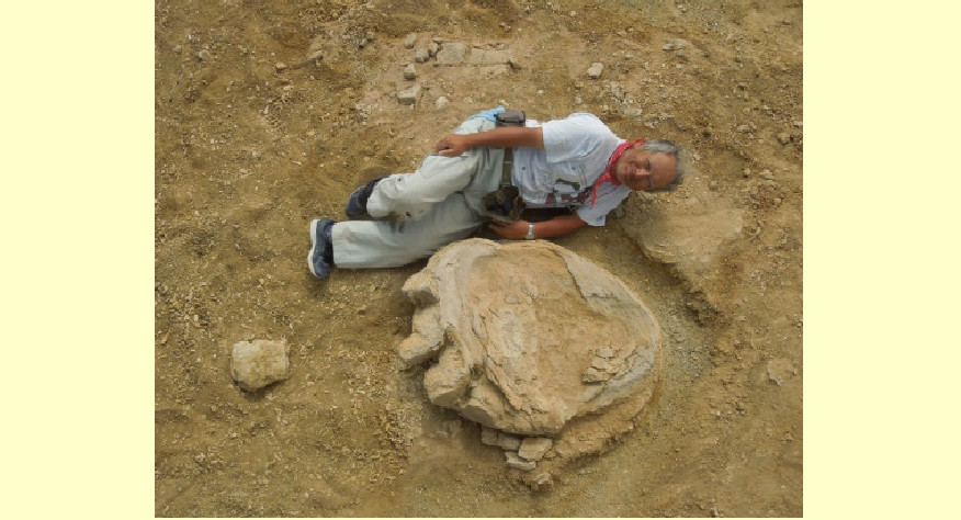 Okajamas universitātes profesors Šinobu Išigaki uzskatāmi demonstrē dinozaura pēdas izmēru.
