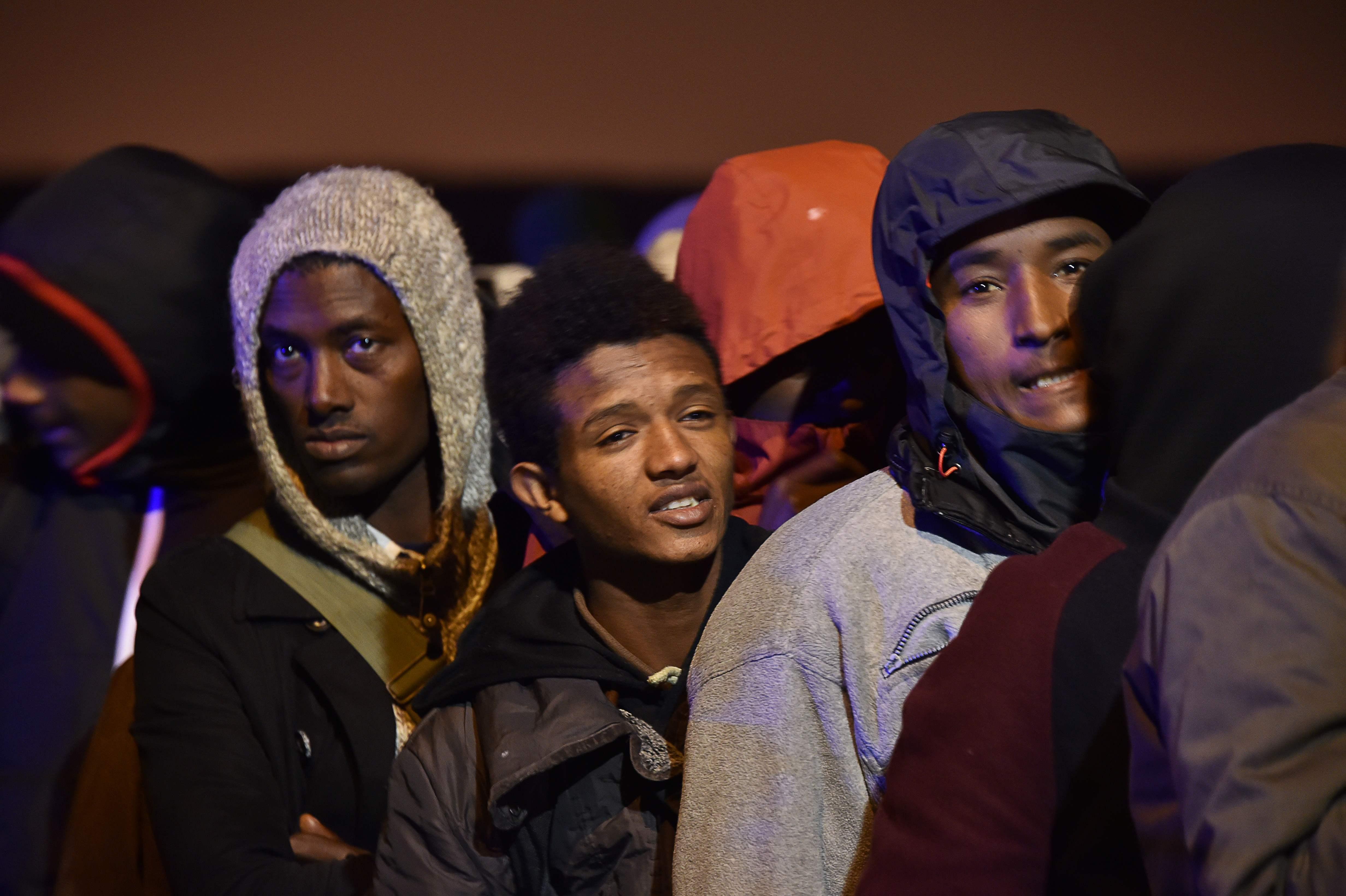 Migranti ar savām personiskajām mantām sākuši pulcēties pie noliktavas, kas kalpo par centrālo punktu nometnes evakuācijas operācijā.