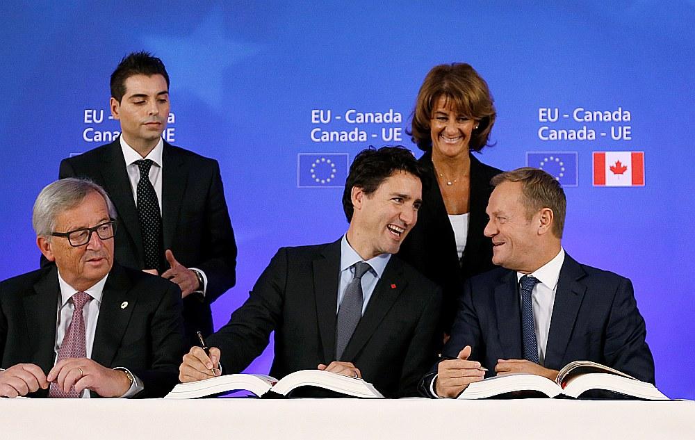 ES vadītāji un Kanādas premjerministrs Džastins Trudo (centrā) paraksta ES un Kanādas brīvās tirdzniecības līgumu.