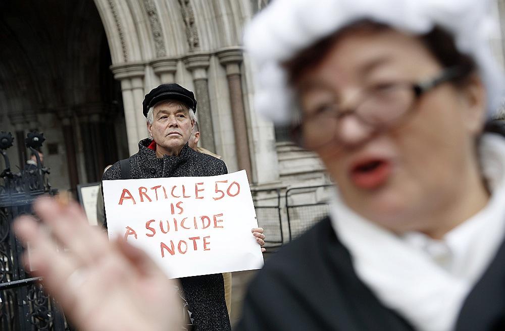 """Politiskās cīņas atbalsojas ielās. """"Brexit"""" atbalstītājs no kustības """"Iedarbini 50. pantu tūlīt!"""" ģērbies kā tiesnesis pie Lielbritānijas Augstākās tiesas. Aizmugurē """"Brexit"""" pretinieks ar plakātu """"50. pants ir pašnāvības zīme""""."""