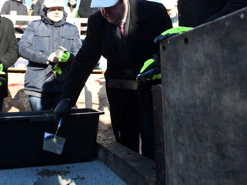 """AS """"Rīgas siltums"""" valdes priekšsēdētājs Normunds Talcis iemūrē kapsulu ar vēstījumu nākamajām paaudzēm biokurināmā katlumājas pamatos Rencēnu ielā."""