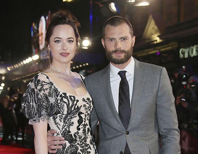 """Filmas """"Tumsa 50 nokrāsās"""" galveno lomu tēlotāji Dakota Džonsone un Džeimijs Dornans pozē fotogrāfiem filmas pirmizrādē Londonā."""