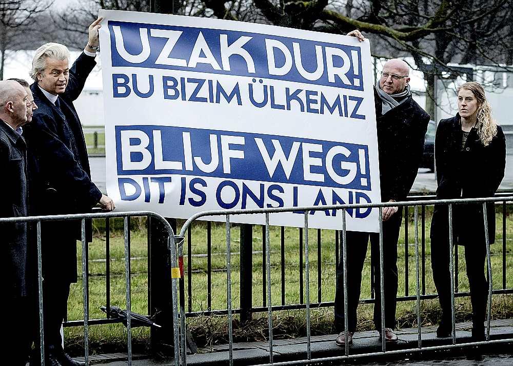 """Nīderlandes galēji labējās Brīvības partijas līderis Gērts Vilderss (no kreisās) pie Turcijas vēstniecības Hāgā protestē pret Turcijas ārlietu ministra Mevlita Čavušolu plānoto uzstāšanos mītiņā, lai aģitētu par prezidenta pilnvaru paplašināšanu Turcijā gaidāmajā referendumā. Vildersa plakāts vēsta: """"Turieties pa gabalu! Šī ir mūsu valsts."""""""