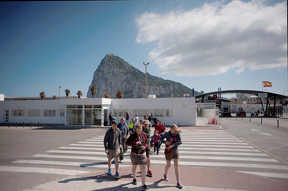 Tūristi šķērso Gibraltāra robežu. Gibraltāra klints (fonā) ir teritorijas galvenā ģeogrāfiskā pazīšanās zīme. Gibraltārs vaino Spāniju garu satiksmes sastrēgumu izraisīšanā šomēnes, veicot stingrāku robežkontroli, ko saista ar politisku spiedienu uz britu teritoriju izstāšanās sakarā.