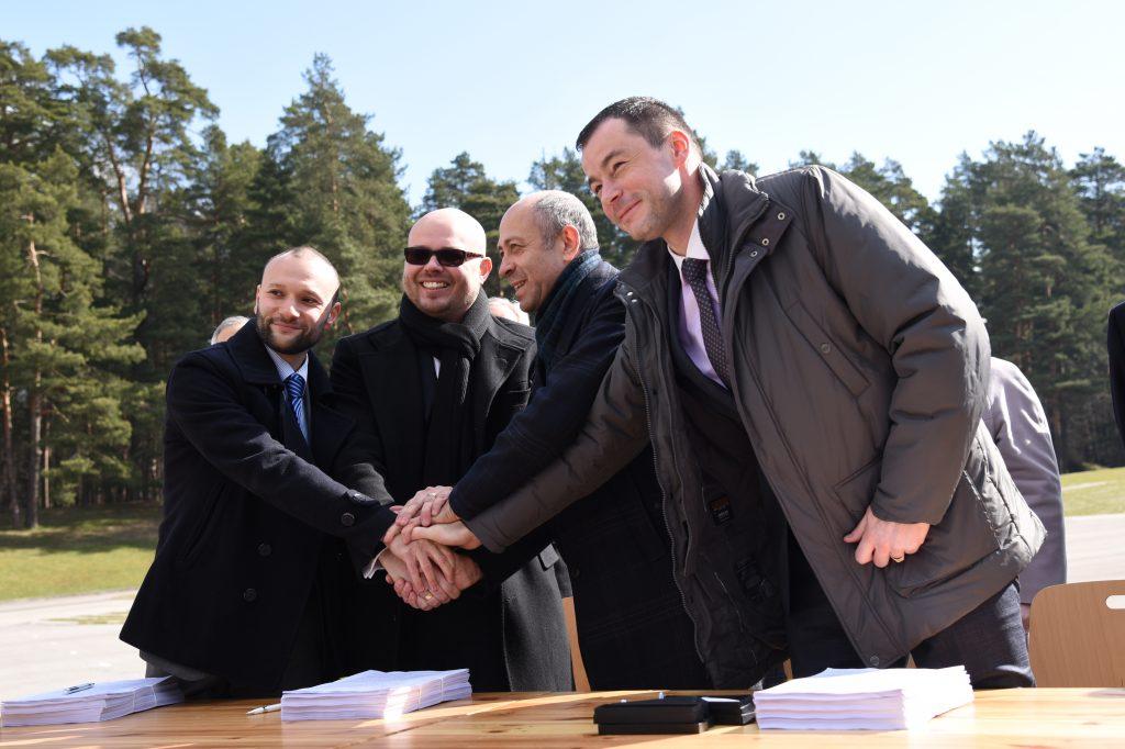 """AS """"LNK Industries"""" valdes locekļi Dāvids Lipkins (no kreisās) un Jevgēņijs Locevs, Rīgas domes Īpašuma departamenta direktors Oļegs Burovs un SIA """"RERE Būve"""" valdes priekšsēdētājs Valdis Koks sarokojas pēc Rīgas domes un pilnsabiedrības """"LNK, RERE"""" līguma par Mežaparka Lielās estrādes rekonstrukciju parakstīšanas uz estrādes skatuves."""