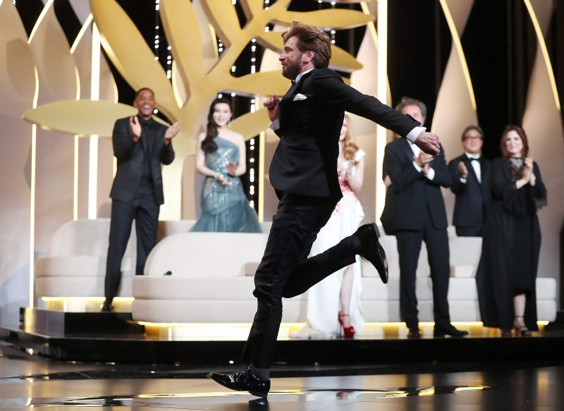 "Zviedru režisors Rubens Ostlunds skriešus dodas saņemt par filmu ""The Square"" nopelnīto ""Zelta palmas zaru""."