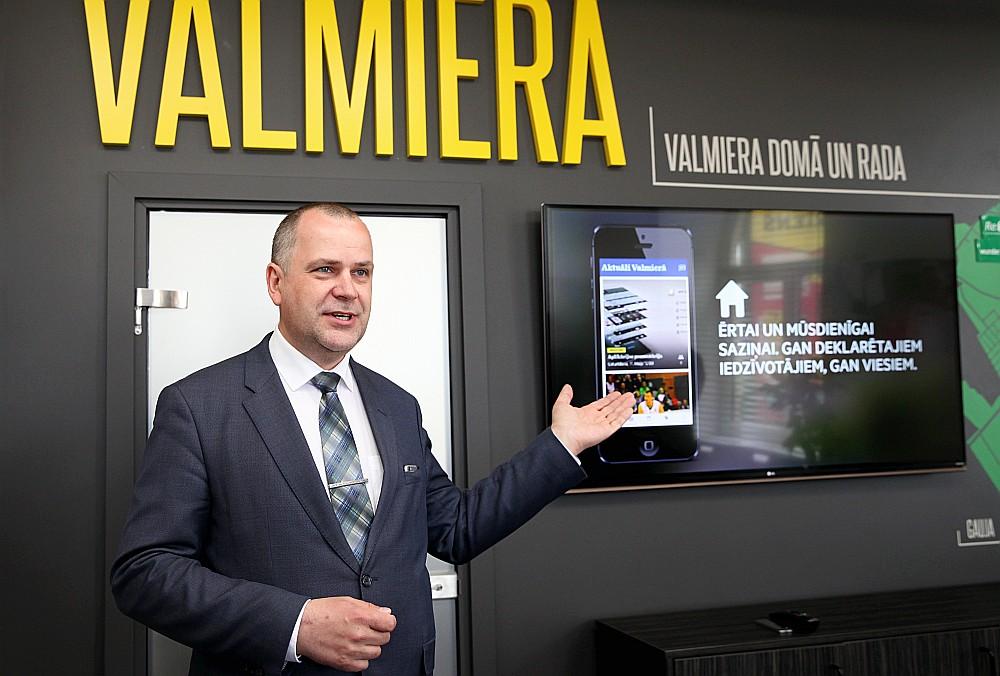 """Valmieras domes priekšsēdētājs Jānis Baiks iepazīstina ar pašvaldības mobilo lietotni """"Mana Valmiera""""."""