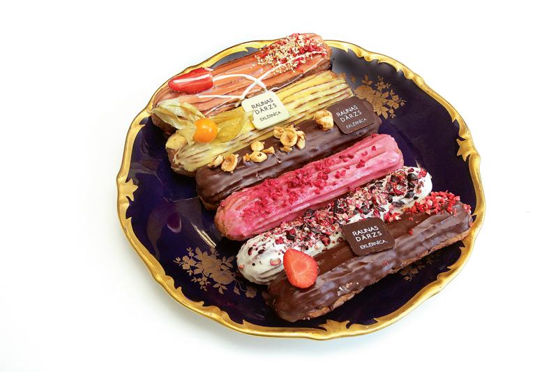 """Daži """"Raunas dārza"""" eklēri tuvplānā: ar zemenēm un tumšo šokolādi, ar upenēm un balto šokolādi, ar avenēm, ar vaniļas krēmu, ar zemenēm un mango, ar lazdu riekstu krēmu, kļavu sīrupā glazētiem riekstiem un tumšo šokolādi."""