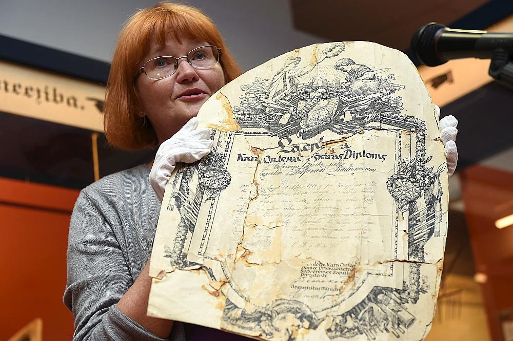 """Aizkraukles Vēstures un mākslas muzeja galvenā krājuma glabātāja Ilzīte Ozoliņa demonstrē Lāčplēša Kara ordeņa diplomu, kuru savulaik dusmās saplēsuši čekisti. Arī šis eksponāts būs aplūkojams izstādē """"Latvijas gadsimts""""."""