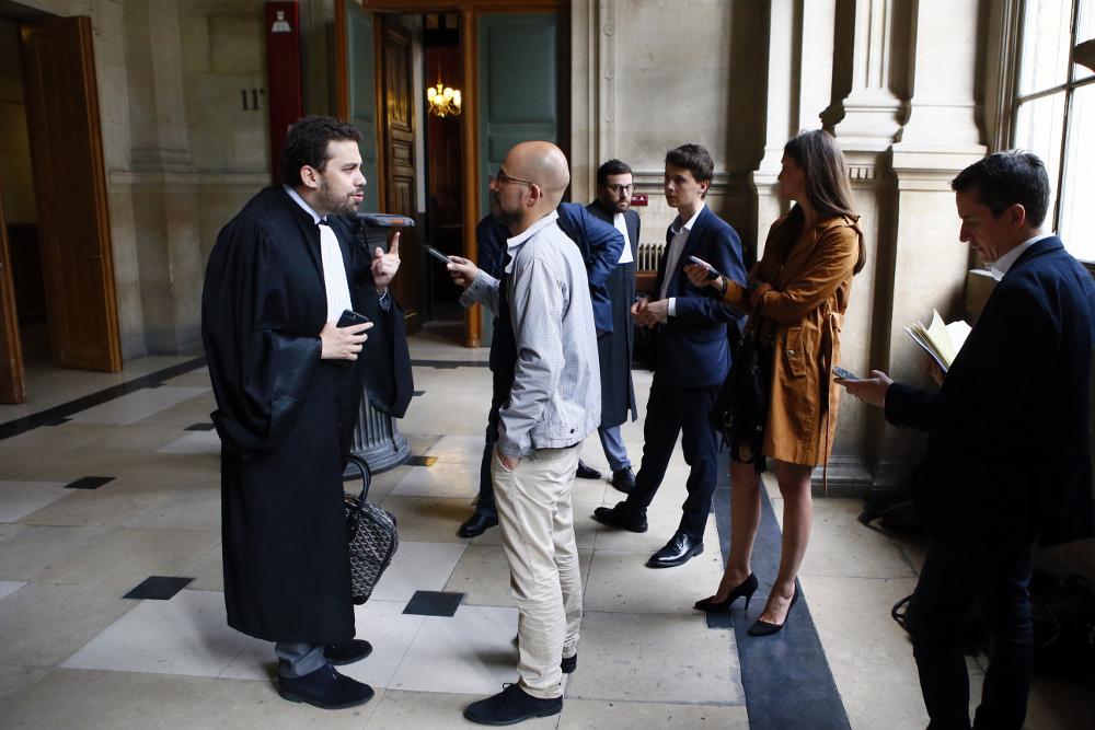"""""""Rietumu bankas"""" advokāts Patriks Klugmans (no kreisās) runā ar plašsaziņas līdzekļu pārstāvjiem pēc tiesas procesa noslēguma."""