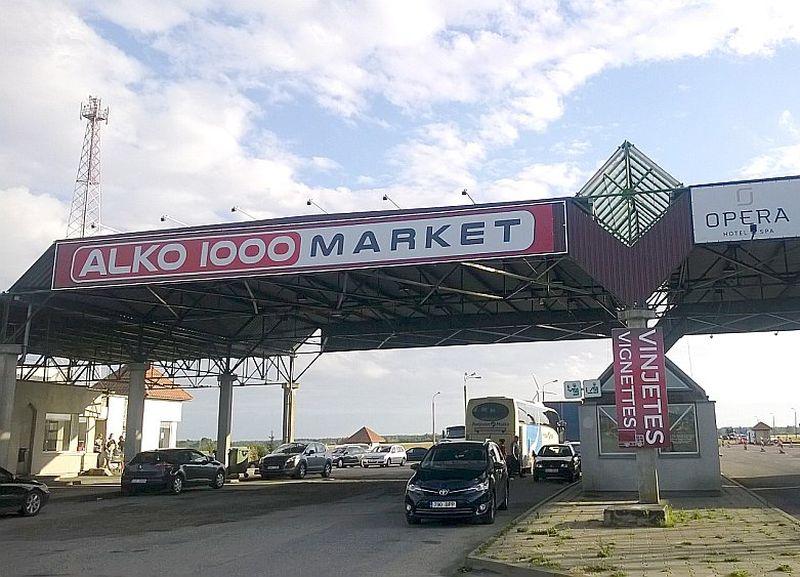"""Reklāma, kas piestiprināta pie jumta malas virs bijušā robežpunkta būdiņām, vēsta, ka tūristi ieradušies valstī """"ALKO 1000 MARKET"""", nevis Latvijā."""